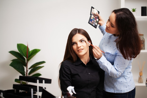 A professional make-up artist makes an evening make-up for a young woman.