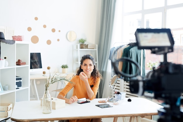 Professional make-up artist shooting new video for her beauty blog channel while staying at home