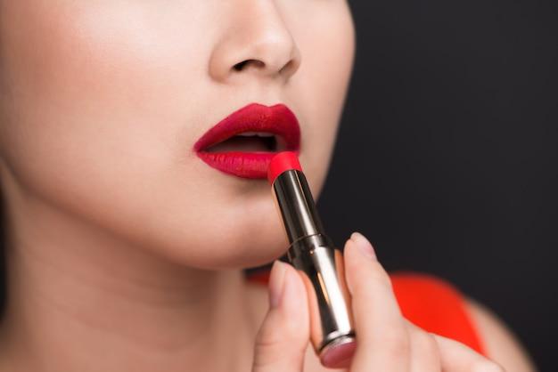 プロのメイク。赤い口紅を塗る魅力的なアジアのモデル。