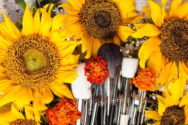木製の背景に美しい野生の花の横にあるプロのメイクアップブラシ