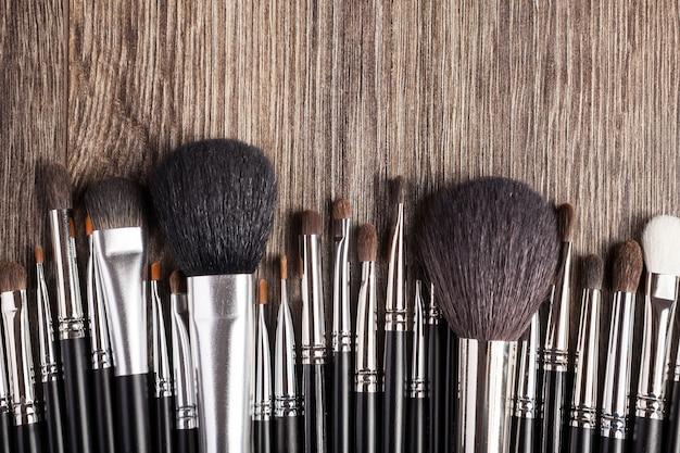 木製の背景にプロのメイクアップブラシ。美容業界
