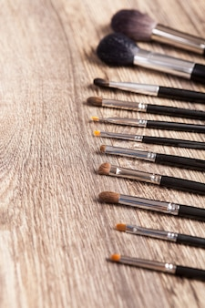 Pennelli trucco professionali su fondo in legno. industria della bellezza