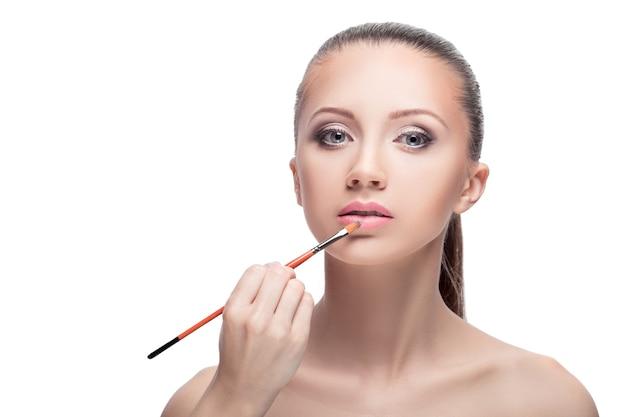 Профессиональный макияж. макияж, мириться. женщина наносит помаду на губы кистью для губ