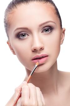 プロのメイク。化粧。リップブラシで唇に口紅を塗る女性