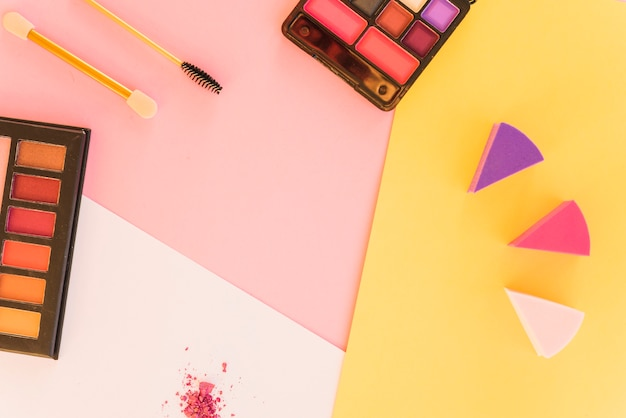 Professional make-up tools and eyeshadow palette on multicolored background