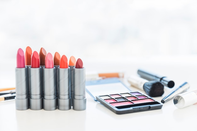 Professional make-up tools with palette of cosmetic eye shadows and row of lipstick shades