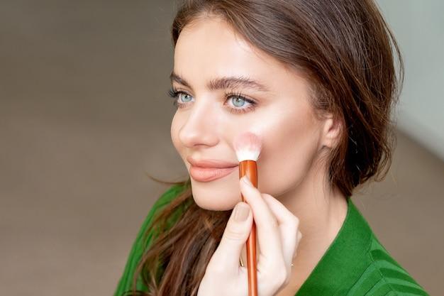 プロのメイクアップアーティストが女性の顔に肌のトーンを適用します。