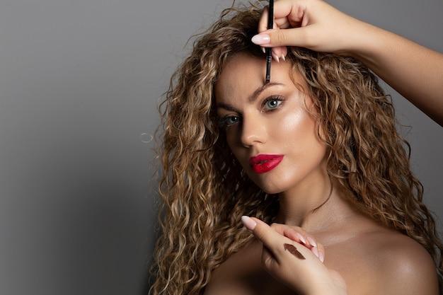 女性の眉毛に眉毛ポマードを塗るプロのメイクアップアーティスト。コピースペース