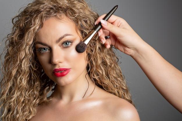 フォトセッションの前に女性の頬骨に蛍光ペンを適用するプロのメイクアップアーティスト