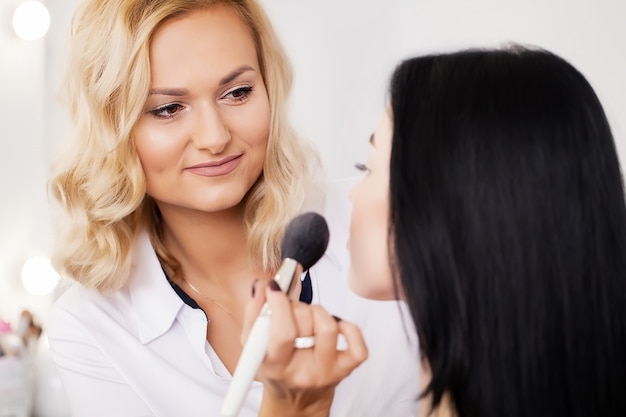 Professional makeup artist applying lipstick