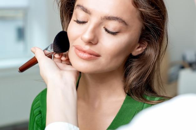 女性の顔に肌のトーンを適用するプロのメイクアップアーティスト。