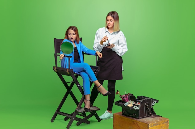 緑のスタジオで女の子にメイクをしているプロのメイクアップアーティスト