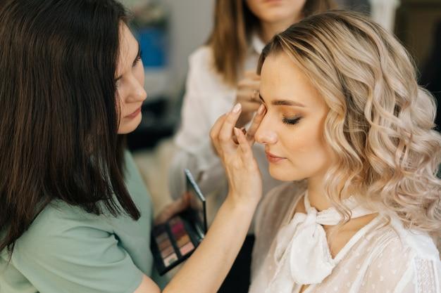 미용사가 젊은 여성을 위해 머리를 하는 동안 얼굴 화장을 하는 전문 메이크업 아티스트
