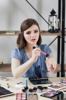 彼女の手でブラシの柔らかさをテストするプロのメイクアップアーティスト