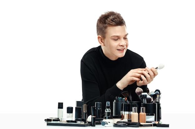 Профессиональный визажист с инструментами, изолированные на белом фоне студии. мужчина в женской профессии. концепция гендерного равенства