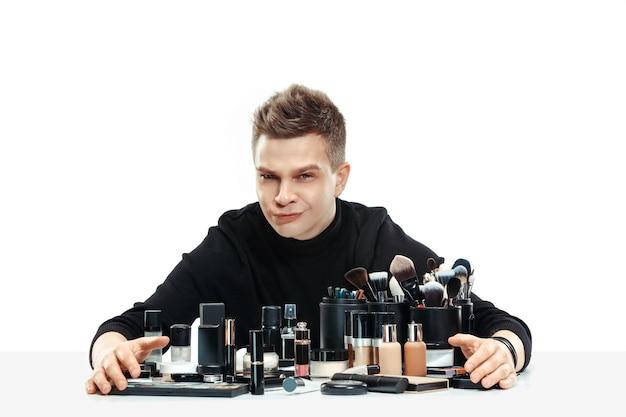 白いスタジオの背景に分離されたツールを持つプロのメイクアップアーティスト。女性の職業の男性。ジェンダー平等の概念