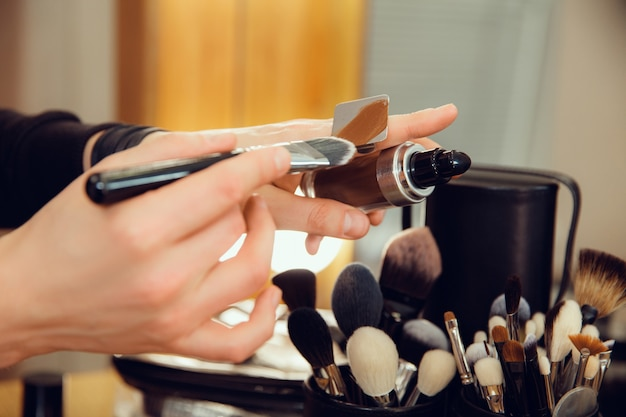 Professional makeup artist working at salon. the man in female proffesion. gender equality concept. male hands with brush closeup