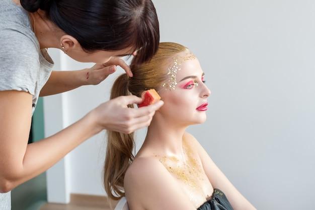 Профессиональный визажист работает с красивой блондинкой молодой женщины. сцена за сценой: мастер креативного макияжа наносит тени для век. красивое женское лицо. макияж подробно. красавица девушка с идеальной кожей