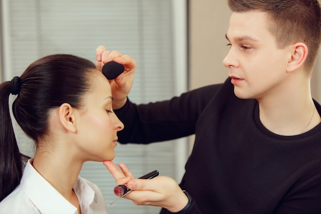 Professional makeup artist working with beautiful young woman. the man in female proffesion. gender equality concept
