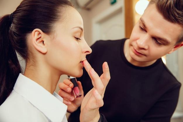 Truccatore professionista che lavora con bella giovane donna.