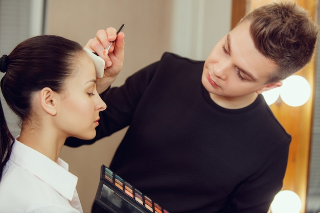 Professional makeup artist working with beautiful young woman.