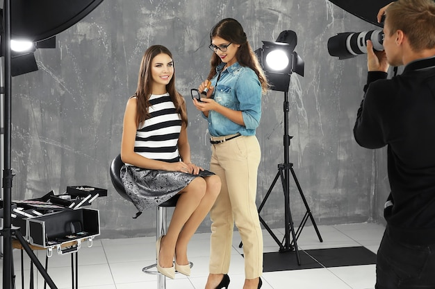 Профессиональный визажист, работающий с молодой красивой женщиной на фотосессии