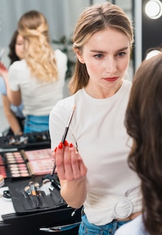 Professional makeup artist working with young woman