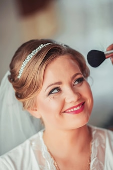 Professional makeup artist working on young bride