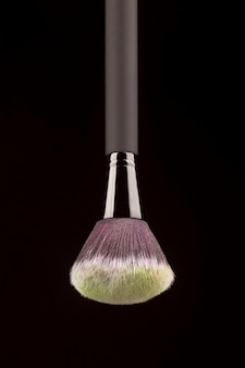 Professional makeup brush with yellow powder on black background
