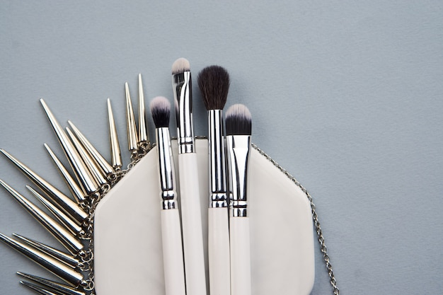 Professional makeup brushes on grey table