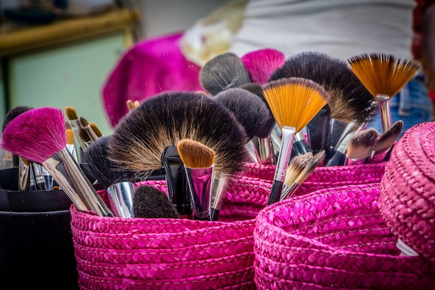 Professional makeup brushes in magenta basket