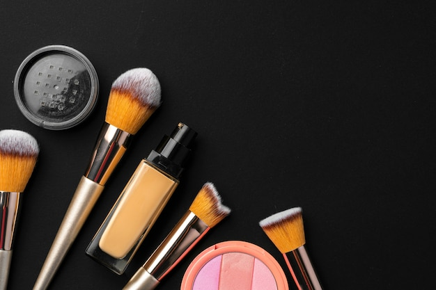Professional makeup brushes and tools, make-up products set on dark table
