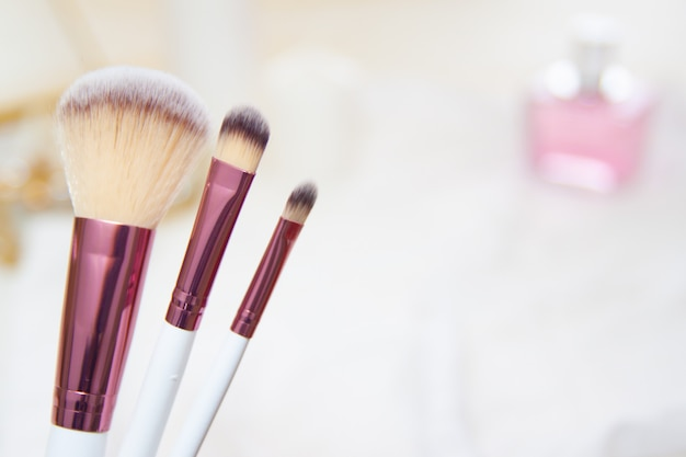 Professional makeup brushes and white pink blurred cosmetics background.