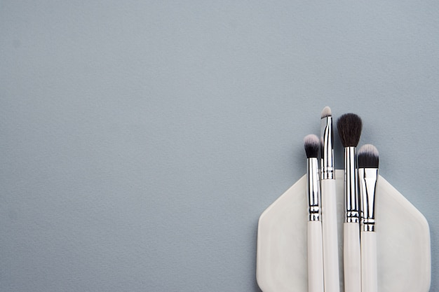 Professional makeup brushes on a white stand on a gray background.