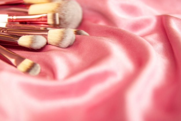 Professional makeup cosmetic brushes on crumpled silk pink wavy fabric background.