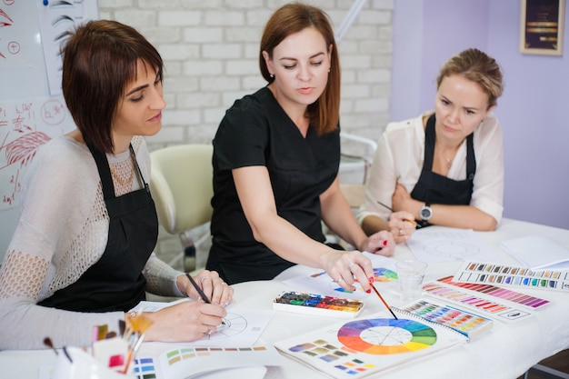 Professional makeup courses. ladies studying colors, using palette, paint and brushes.