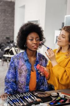 Профессиональный макияж. светловолосый позитивный стилист, который делает макияж темнокожей модели.