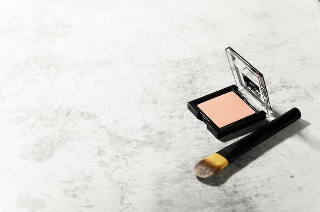 Товары для профессионального макияжа. пудра для лица в открытом квадратном футляре и кисть.