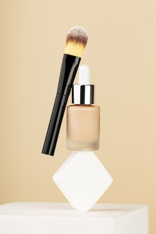 Professional makeup products levitate and balance on white sponge on stand. bottle foundation liquid bb cream, accessory cosmetology brush on beige background. beauty cosmetics for perfect face skin.