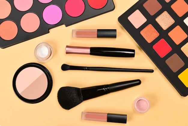 ベージュの背景に化粧品の美容製品、アイシャドウ、顔料、口紅、ブラシ、ツールを備えたプロのメイクアップ製品。テキストやデザインのためのスペース。