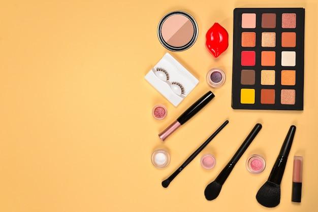 베이지 색 배경에 화장품 미용 제품, 아이섀도, 안료, 립스틱, 브러쉬 및 도구가있는 전문 메이크업 제품. 텍스트 또는 디자인을위한 공간.