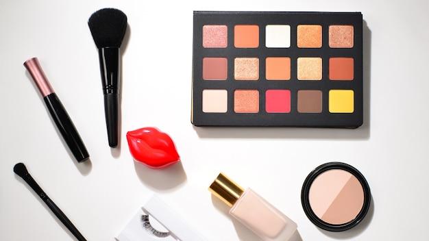 化粧品美容製品、アイシャドウ、顔料、口紅、ブラシ、ツールを備えたプロのメイクアップ製品。テキストやデザインのためのスペース。