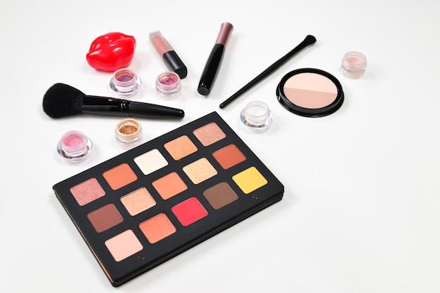 미용 미용 제품, 아이 섀도우, 안료, 립스틱, 브러시 및 도구가 포함 된 전문 메이크업 제품입니다. 텍스트 또는 디자인을위한 공간.