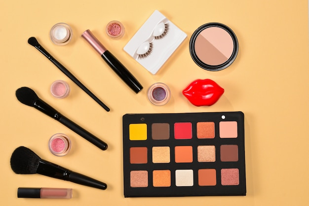 Professional makeup products with cosmetic beauty products, eye shadows, pigments, lipsticks, brushes and tools on beige background. space for text or design.