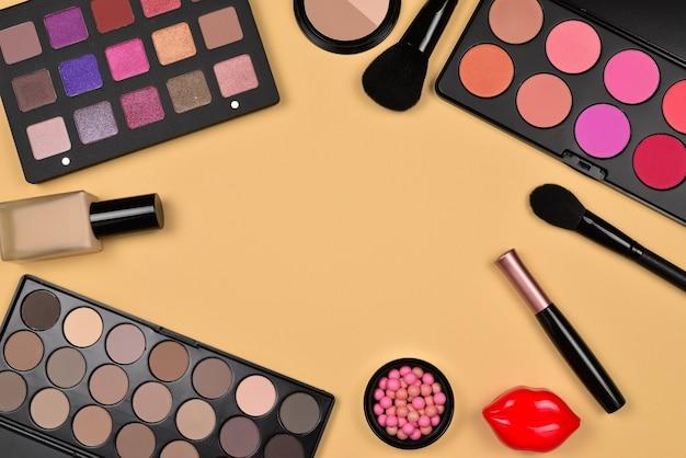 Профессиональная косметическая продукция с косметическими продуктами, тональным кремом, губной помадой, тенями для век, ресницами, кистями и инструментами.