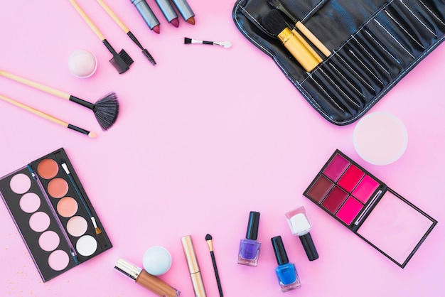 Professional makeup products with cosmetic beauty products on pink background