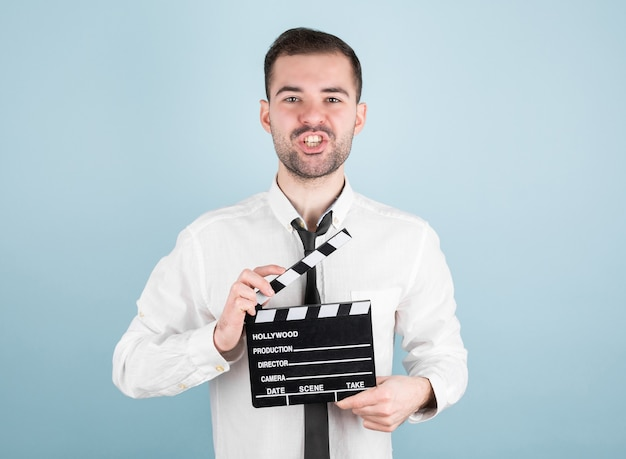 Professional male actor ready for shooting film, holds movie clapper, isolated on blue wall.