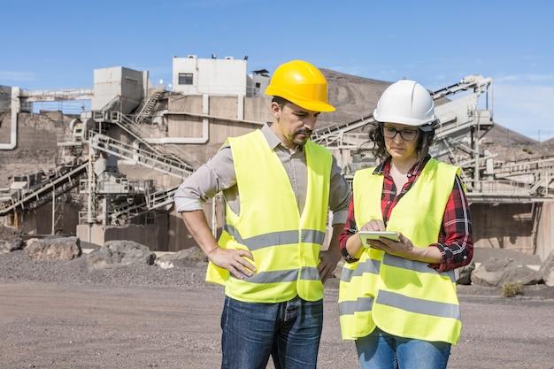 건설 현장에서 작업 문제를 논의하면서 태블릿에서 정보를 확인하는 안전모와 조끼를 입은 전문 남성 및 여성 엔지니어