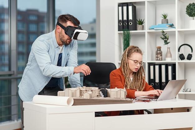 Профессиональный архитектор-мужчина в очках дополненной реальности, работающий с макетом здания, и женщина-коллега с ноутбуком
