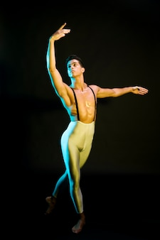 Professional male ballet dancer performing in spotlight